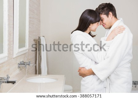 Young couple in bathrobe standing face to face at home in the bathroom - stock photo