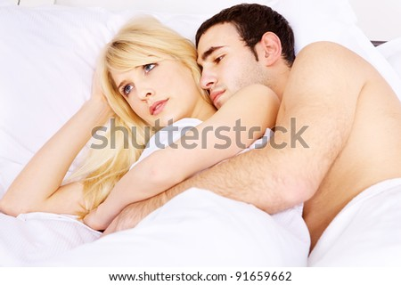 Young couple in bed, he embracing her, focus on woman - stock photo