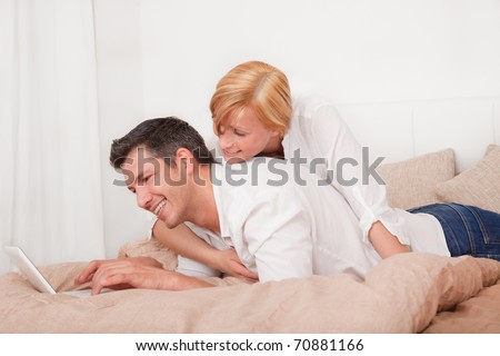 Young couple in bed surfing internet with netbook computer laptop