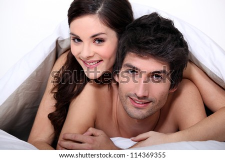 Young couple in bed together - stock photo
