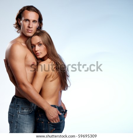Young couple in blue jeans on blue background - stock photo
