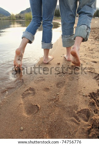 young couple in blue jeans walking on beach