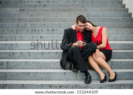 Young couple in business clothes outdoor - man working with smartphone and woman relaxing - stock photo
