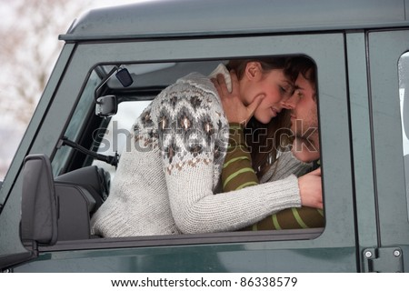 Young couple in car in snow