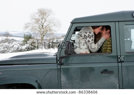 Young couple in car in snow - stock photo