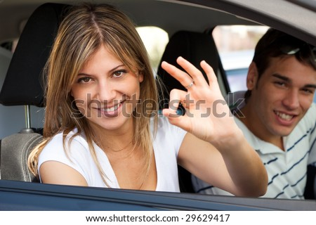 young couple in car showing okay sign - stock photo