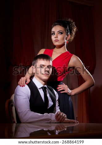Young couple in dark room - stock photo