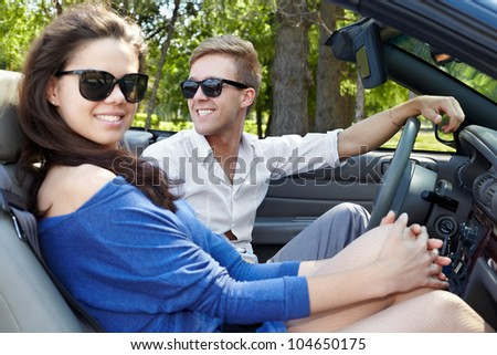 Young couple in dark sunglasses sits in a cabriolet, focus on a boy - stock photo