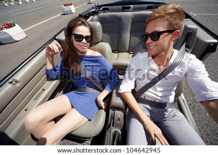 Young couple in dark sunglasses, sitting fastened with seatbelts on front seats of convertible - stock photo