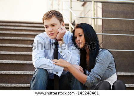 Young couple in depression sitting on the steps - stock photo