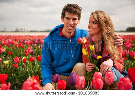 Young couple in Dutch flower fields with colorful tulips - stock photo