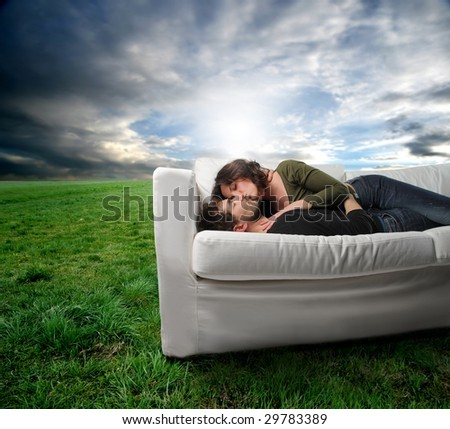 young couple in effusion on a sofa in a grass field - stock photo