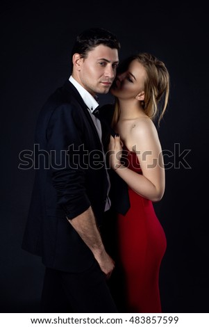 Young couple in evening gown in black background