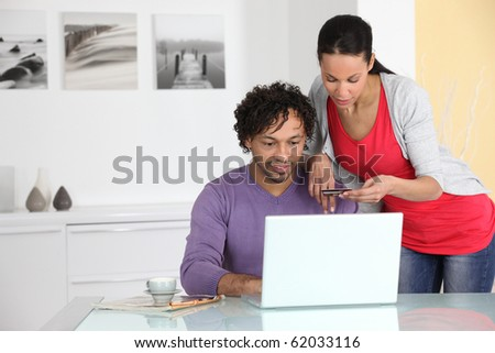 Young couple in front of computer at home