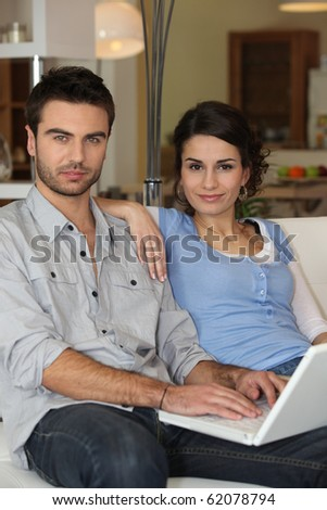 Young couple in front of computer at home - stock photo