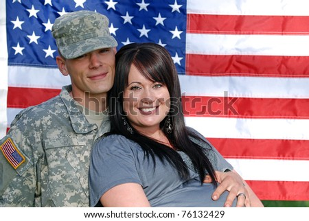 Young couple in front of the United States flag. Young man is in the military. - stock photo