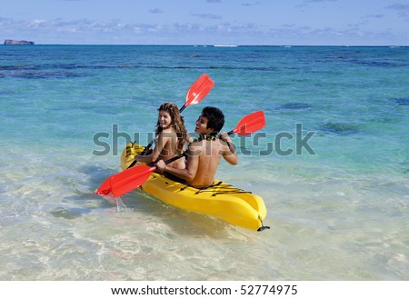 young couple in hawaii paddling a kayak - stock photo