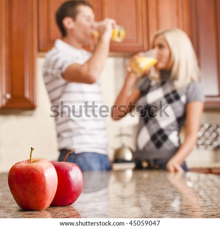 Young couple in kitchen drinking a glass of orange juice, two apples on counter in foreground. Square format. - stock photo