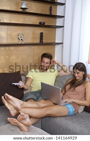 Young couple in living room, girl browsing internet on laptop, guy watching tv. - stock photo