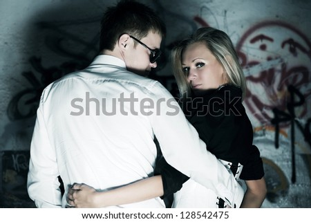 Young couple in love against a graffiti - stock photo