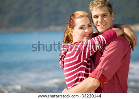 young couple in love and hugging on beach