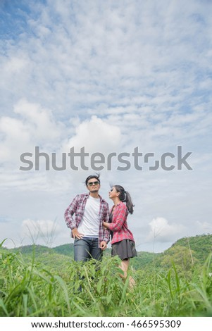 Young couple in love at  Beautiful morning sky on the Mountain