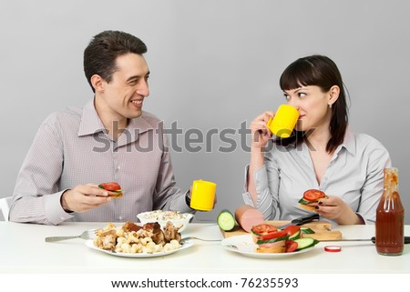 young couple in love at home eating together on kitchen - stock photo