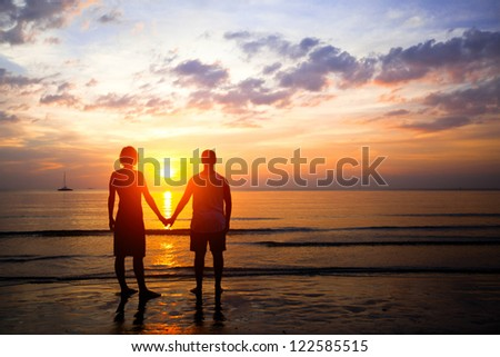 Young couple in love at sunset on the seashore - stock photo