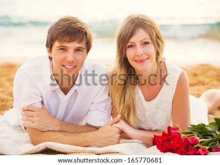 Young couple in love, Attractive man and woman enjoying romantic date at the beach at sunset - stock photo