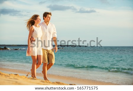 Young couple in love, Attractive man and woman enjoying romantic evening walk on the beach,  Watching the sunset