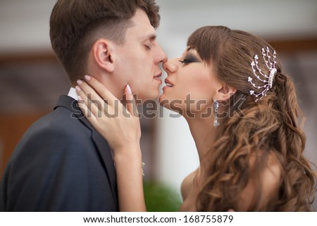 Young couple in love bride and groom kissing at wedding day at restaurant. Newlywed man and woman posing at marriage day in cafe interior.