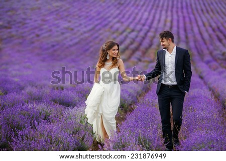 Young couple in love bride and groom, wedding day in summer. Enjoy a moment of happiness and love in a lavender field. Bride in a luxurious wedding dress. - stock photo