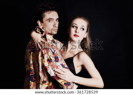 Young couple in love dancing on black background