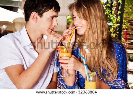 young couple in love drinking juice, outdoor shot - stock photo