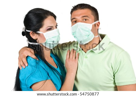 Young couple in love embracing but wearing protective mask also ,concept of pretection from swine flu
