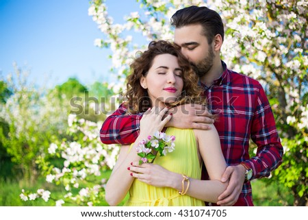 young couple in love embracing in summer park