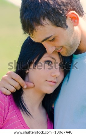 Young couple in love embracing outdoors in a sunny day - stock photo