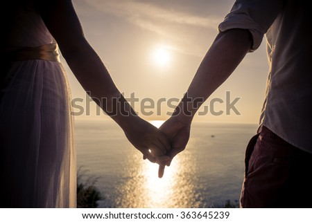 Young couple in love enjoying the view on a cape in Thailand. Honeymoon vacation in a tropical warm place