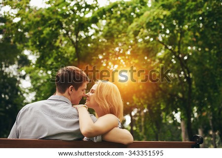 Young couple in love enjoying their time when sitting on the bench in park - stock photo