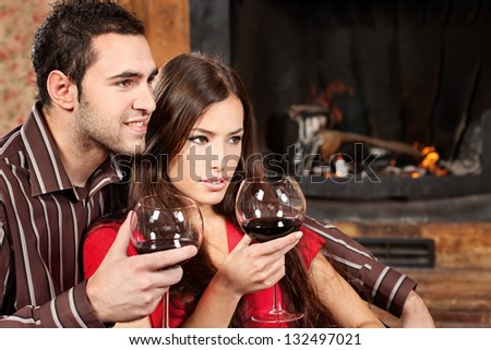Young couple in love enjoying wine near fireplace - stock photo