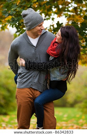 Young couple in love frolicking in a park