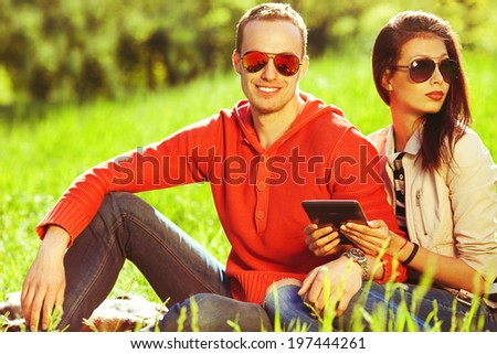 Young couple in love having fun in the autumn park, sitting together and using tablet. Trendy casual clothing and stylish eyewear. Perfect make-up & white shiny smile. Outdoor shot - stock photo