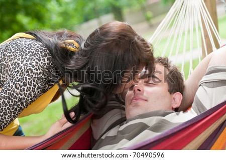 Young couple in love having intimate time outdoors - detail of girl bending over boy - stock photo