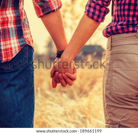 Young couple in love holding hands, tranquil scene, face is not visible - stock photo