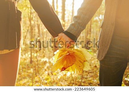Young couple in love holding hands with leaves in autumn park, face is not visible - stock photo