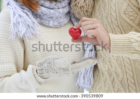 Young couple in love holding small red heart outdoors in winter - stock photo