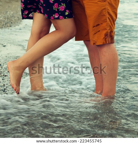 Young couple in love hugging and kissing on the beach. Two lovers man and woman barefoot in the water. Summer in love.