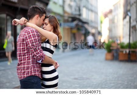 Young couple in love, hugging on the street - stock photo