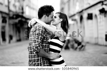 Young couple in love, hugging on the street. Selective focus. - stock photo