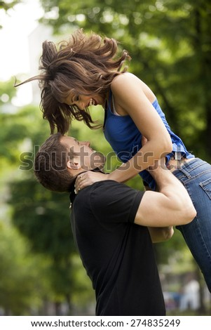 Young couple in love, hugging, she is jumping,he is holding her in embrace - stock photo